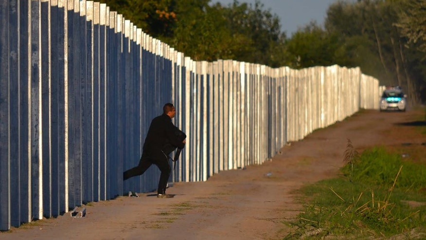 In this Sept. 7, 2015 file photo a migrant runs after he enters the territory of Hungary by crossing the temporary protection fence along the Hungarian-Serbian border as a Hungarian police car approaches at Roszke, 180 kms southeast of Budapest, Hungary. Thousands of migrants have continued to travel through Hungary on their way toward western Europe, despite fences, border closures and the European Union's deal with Turkey to stop sea crossings to Greece. (Edvard Molnar/MTI via AP, file)