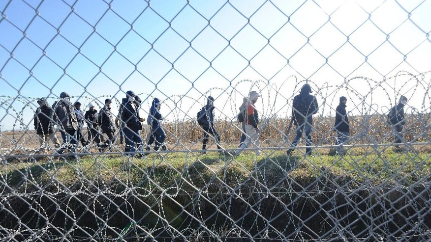 FILE - In this Feb. 22, 2016 file photo migrants walk behind a temporary protective fence at the border between Hungary and Serbia near Morahalom, 179 kms southeast of Budapest, Hungary. Thousands of migrants have continued to travel through Hungary on their way toward western Europe, despite fences, border closures and the European Union's deal with Turkey to stop sea crossings to Greece. (Zoltan Gergely Kelemen/MTI via AP, file)
