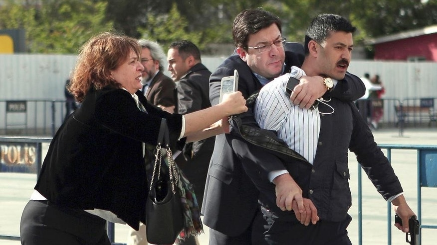 Dilek Dundar, journalist Can Dundar's wife, and his lawyer, 2nd left, overpower a gunman just after the attack  on Can Dundar outside city's main courthouse in Istanbul, Friday, May 6, 2016. A man shouted ìtraitorî and fired two shots  prominent Turkish journalist Can Dundar outside a courthouse where he is on trial accused of revealing state secrets for his reports on alleged government arms smuggling to Syria. Can Dundar, editor-in-chief of opposition Cumhuriyet newspaper, escaped the attack unhurt, but Yavuz Senkal, a journalist working for private NTV television was slightly injured in the leg. (Can Erok, Cumhuriyet via AP) TURKEY OUT