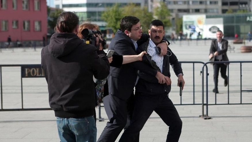 "Dilek Dundar, journalist Can Dundar's wife,  partially obscured by cameraman, and his lawyer, 2nd right, overpower a gunman just after the attack  on Can Dundar outside city's main courthouse in Istanbul, Friday, May 6, 2016. A man shouted ""traitor"" and fired two shots  prominent Turkish journalist Can Dundar outside a courthouse where he is on trial accused of revealing state secrets for his reports on alleged government arms smuggling to Syria. Can Dundar, editor-in-chief of opposition Cumhuriyet newspaper, escaped the attack unhurt, but Yavuz Senkal, a journalist working for private NTV television was slightly injured in the leg. (Can Erok, Cumhuriyet via AP) TURKEY OUT"