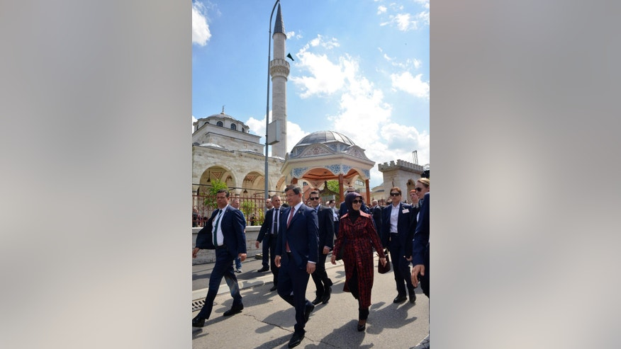 Turkish Prime Minister Ahmet Davutoglu walks in front of the Ferhat Pasha mosque after its official opening ceremony, in Banja Luka, Bosnia, on Saturday May 7, 2016. Over 10,000 people turned out Saturday for the re-opening of a mosque in Bosnia that was blown up by Christian Orthodox Serbs during the 1992-1995 war and that became a symbol of the effort to destroy Bosnia's centuries-long multireligious fabric. (AP Photo/Radivoje Pavicic)