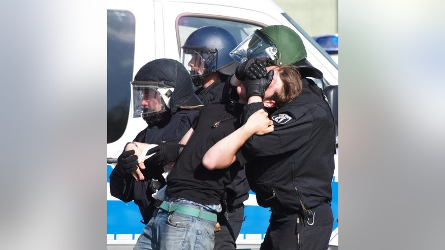 German police arrest a counter-protester against a right-wing extremists' demonstration in front of the chancellery in Berlin, Germany, Saturday, May 7, 2016. About 1,000 right-wingers have rallied outside Berlin's main train station, protesting Chancellor Angela Merkel's welcoming stance to refugees. (AP Photo/David Rising)