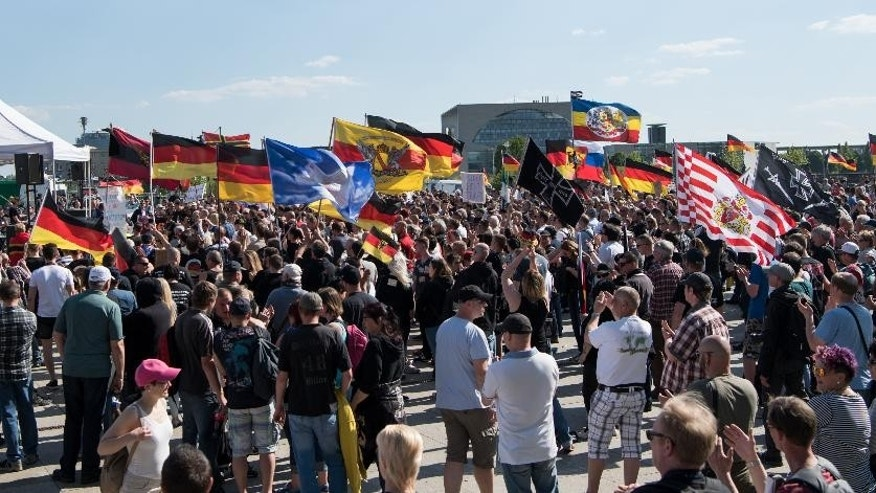 Participants of  right-wing groups stand in front of the main train station inBerlin,Germany, Saturday, May 7, 2016. About 1,000 right-wing extremists have rallied, protesting Chancellor Angela Merkel's welcoming stance to refugees. (Bernd von Jutrczenka/dpa via AP)