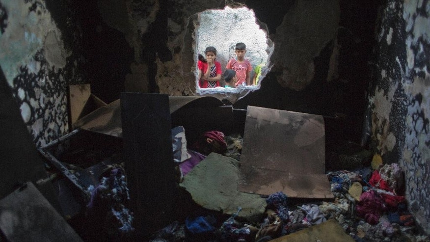 Palestinian children look through a hole in a wall at a burned bedroom where three children were killed by candle sparked on their family house in the Shati refugee camp in Gaza City, Saturday, May 7, 2016. Three Palestinian children have been killed in a Gaza house fire started by a candle, sparking internal finger-pointing over the coastal territory's lingering power crisis. (AP Photo/ Khalil Hamra)