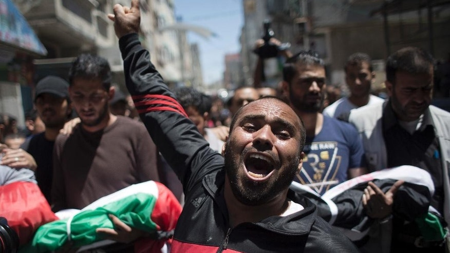 A Palestinian man chants angry slogans during the funeral of three children who were killed in a fire caused by candle in the Shati refugee camp in Gaza City, Saturday, May. 7, 2016. Three Palestinian children have been killed in a Gaza house fire started by a candle, sparking internal finger-pointing over the coastal territory's lingering power crisis.  (AP Photo/ Khalil Hamra)