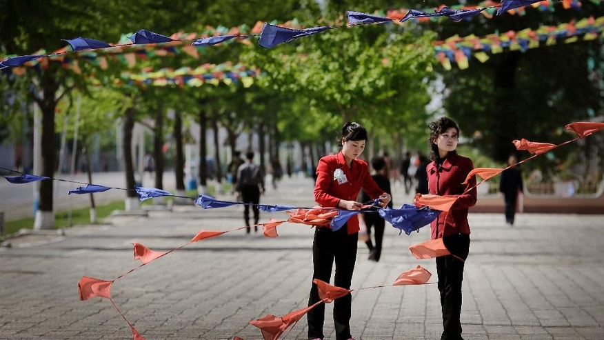 North Korean women tie flags as they decorate the streets in downtown Pyongyang, North Korea Saturday, May 7, 2016. North Korean leader Kim Jong Un hailed his country's recent nuclear test to uproarious applause as he convened the first full congress of its ruling party since 1980, an event intended to showcase the North's stability and unity in the face of tough international sanctions and deepening isolation. (AP Photo/Wong Maye-E)