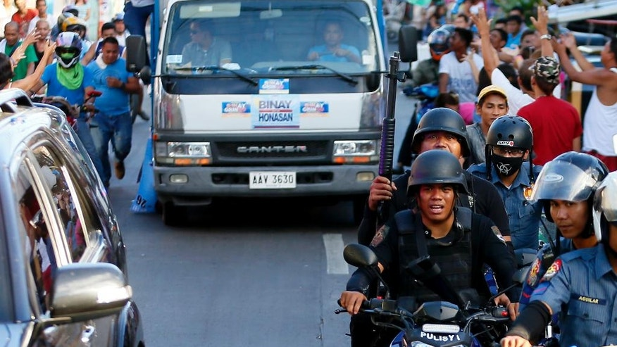 SWAT members of the Philippine National Police provide security to the campaign motorcade of presidential candidate Vice-president Jejomar Binay and congressman Manny Pacquiao, who is running for senator in Monday's national elections during their campaign rally in Navotas north of Manila, Philippines, Friday, May 6, 2016. Boxing star Manny Pacquiao pressed on with his campaign for a seat in the Philippine Senate despite a reported militant plot to kidnap him. (AP Photo/Bullit Marquez)