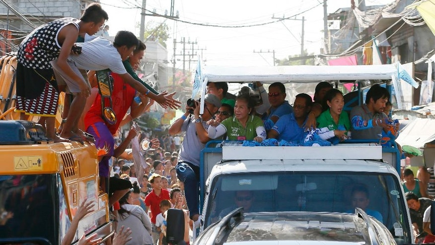 Presidential candidate Vice-president Jejomar Binay, center, and Congressman Manny Pacquiao, right, who is running for senator in Monday's national elections, throw souvenir t-shirts, candies and wrist bands to supporters during their campaign sortie in Navotas north of Manila, Philippines Friday, May 6, 2016. Binay is running fourth in the latest poll survey while Pacquiao is in the top five of the possible senators. (AP Photo/Bullit Marquez)