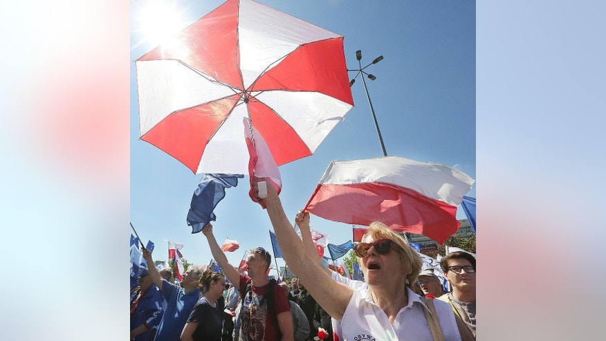 Opponents of Poland's government march downtown streets to protest the country's direction under a conservative government that is accused of eroding the rule of law, in Warsaw, Poland, Saturday, May 7, 2016. The protest is also meant as a show of support for European values and the country's membership in the EU. (AP Photo/Czarek Sokolowski)