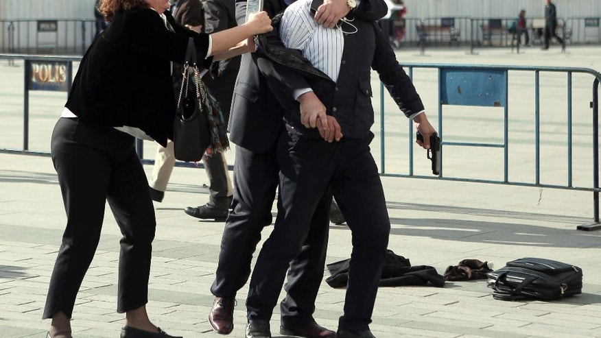 "Dilek Dundar, journalist Can Dundar's wife, and his lawyer, 2nd left, overpower a gunman just after the attack  on Can Dundar outside city's main courthouse in Istanbul, Friday, May 6, 2016. A man shouted ""traitor"" and fired two shots  prominent Turkish journalist Can Dundar outside a courthouse where he is on trial accused of revealing state secrets for his reports on alleged government arms smuggling to Syria. Can Dundar, editor-in-chief of opposition Cumhuriyet newspaper, escaped the attack unhurt, but Yavuz Senkal, a journalist working for private NTV television was slightly injured in the leg. (Can Erok, Cumhuriyet via AP) TURKEY OUT"