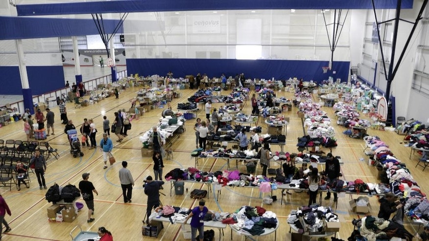 Wildfire evacuees sort through clothes and other items at an evacuation center in Lac La Biche, Alberta, Saturday, May 7, 2016. More than 4,000 wildfire evacuees have come through the center this week.  (AP Photo/Rachel La Corte)