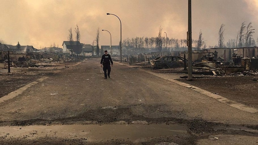 In this May 5, 2016 photo provided by the Royal Canadian Mounted Police Alberta, an RCMP officer surveys the damage on a street in fire-ravaged Fort McMurray, Alberta. More than 80,000 people have left Fort McMurray, in the heart of Canada's oil sands as a wildfire that has devastated the area exploded in size.  (Royal Canadian Mounted Police Alberta via The Canadian Press via AP) MANDATORY CREDIT