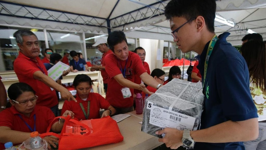 Election workers distribute voting equipment in suburban Quezon city, north of Manila, Philippines on the eve of election day Sunday, May 8, 2016. Thirty years after emerging from a brutal dictatorship, Filipinos will face a dilemma when they pick a new leader on Monday: Should they choose a toughie mayor with an audacious promise to wipe out crimes and graft within months or back reformists who would not be as bold but say they wouldn't put democracy at risk. (AP Photo/Aaron Favila)
