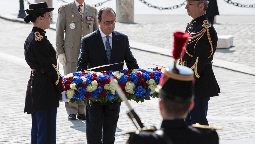 French President Francois Hollande, center, lays a wreath at the Tomb of the Unknown Soldier during commemorations at the Arc de Triomphe marking the 71st anniversary of the end of World War II, in Paris, France, Sunday, May 8, 2016. Victory in Europe Day is celebrated on May 8 to mark the date in 1945 that WWII ended in Europe following Nazi Germany's surrender of its armed forces. (AP Photo/Kamil Zihnioglu, Pool)