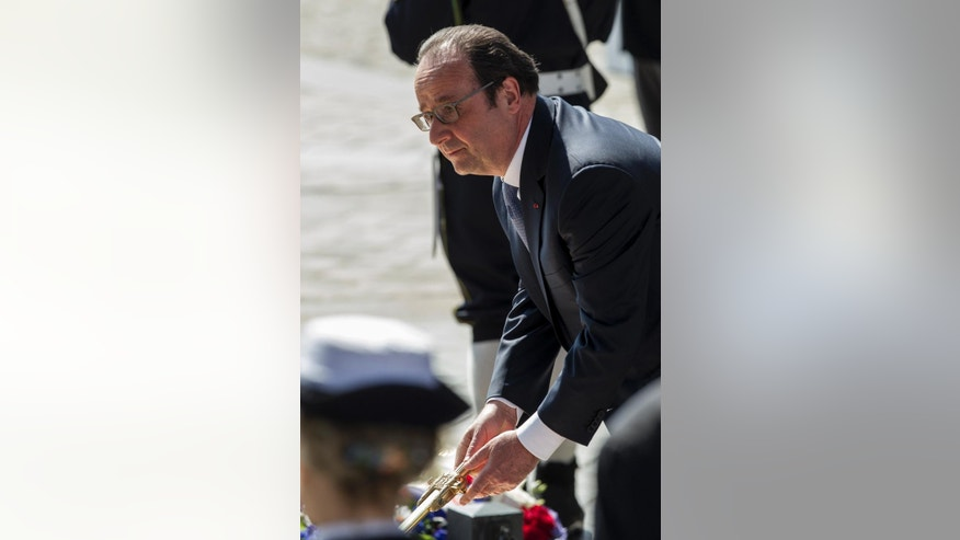 French President Francois Hollande re-kindles the eternal flame at the Tomb of the Unknown Soldier during commemorations at the Arc de Triomphe marking the 71st anniversary of the end of World War II, in Paris, France, Sunday, May 8, 2016. Victory in Europe Day is celebrated on May 8 to mark the date in 1945 that WWII ended in Europe following Nazi Germany's surrender of its armed forces. (AP Photo/Kamil Zihnioglu, Pool)