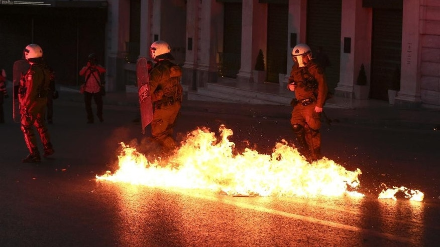A petrol bomb explodes in front of policemen during clashes in Athens, on Sunday, May 8, 2016. Protesters in Greece have hurled firebombs and other projectiles at police in front of parliament before a controversial vote on an austerity bill. (AP Photo/Yorgos Karahalis)