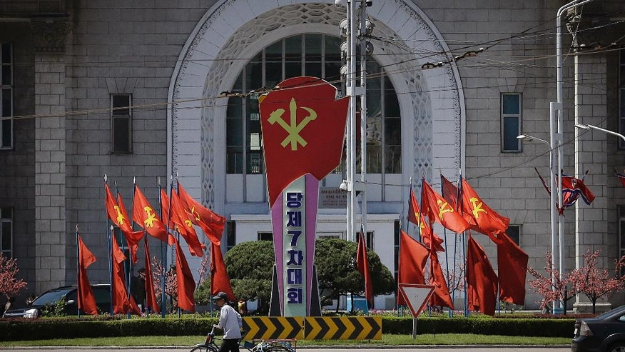 A man pushes his bicycle past the Pyongyang train station which is decorated with the ruling Workers' Party flags Sunday, May 8, 2016, in Pyongyang, North Korea. North Korean leader Kim Jong Un said during a critical ruling party congress that his country will not use its nuclear weapons first unless its sovereignty is invaded. He also announced a five-year plan starting this year to develop the North's dismal economy and identified improving the country's power supply and increasing its agricultural and light-manufacturing production as the critical parts of the program, state media reported. (AP Photo/Wong Maye-E)