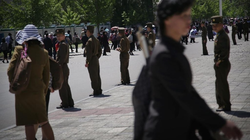 North Korean soldiers stand by a sidewalk while people carrying decorative flowers make their way from the Kim Il Sung Square Sunday, May 8, 2016, in Pyongyang, North Korea. North Korean leader Kim Jong Un said during a critical ruling party congress that his country will not use its nuclear weapons first unless its sovereignty is invaded. He also announced a five-year plan starting this year to develop the North's dismal economy and identified improving the country's power supply and increasing its agricultural and light-manufacturing production as the critical parts of the program, state media reported. (AP Photo/Wong Maye-E)