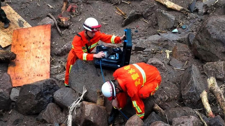 Rescuers use detectors to scan for potential survivors at the site following a landslide in Taining county in southeast China's Fujian province, Sunday, May 8, 2016. Rescuers on Sunday searched for 34 construction workers missing in a landslide at the site of a hydropower project following days of heavy rain in southern China. Seven other workers were pulled out alive, officials and state-run media reported. (Chinatopix via AP) CHINA OUT