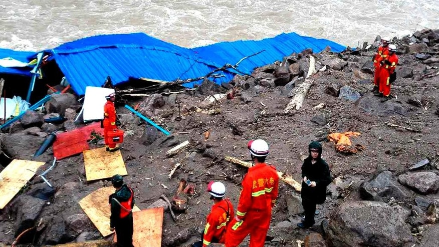 Rescuers look at a damaged building as they search for potential survivors at the site following a landslide in Taining county in southeast China's Fujian province, Sunday, May 8, 2016. Rescuers on Sunday searched for 34 construction workers missing in a landslide at the site of a hydropower project following days of heavy rain in southern China. Seven other workers were pulled out alive, officials and state-run media reported. (Chinatopix via AP) CHINA OUT