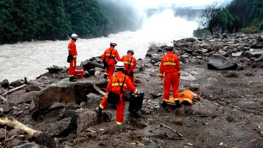Rescuers search for potential survivors at the site following a landslide in Taining county in southeast China's Fujian province, Sunday, May 8, 2016. Rescuers on Sunday searched for 34 construction workers missing in a landslide at the site of a hydropower project following days of heavy rain in southern China. Seven other workers were pulled out alive, officials and state-run media reported. (Chinatopix via AP) CHINA OUT