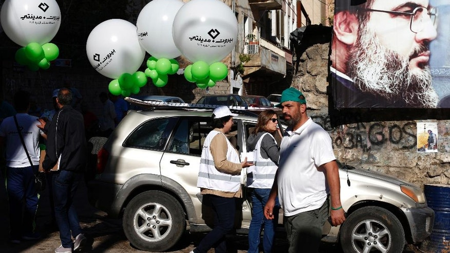 Beirut Madinati campaign workers hold balloons next to a poster showing Hezbollah leader Hassan Nasrallah , outside a polling station during the municipal elections in Beirut, Lebanon, Sunday, May 8, 2016. (AP Photo/Hassan Ammar)