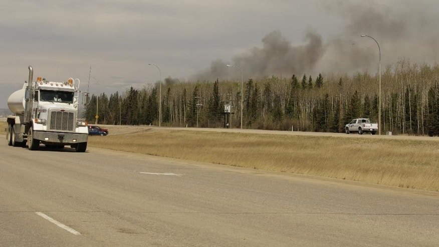 "A truck drives by smoke from a wildfire near Fort McMurray, Alberta on Sunday, May 8, 2016. Officials said Sunday they have completed the transport of thousands of evacuees and reached a turning point in fighting a massive wildfire, hoping to get a ""death grip""' on the blaze that devastated Canada's oil sands town of Fort McMurray amid cooler temperatures.  (AP Photo/Rachel La Corte)"