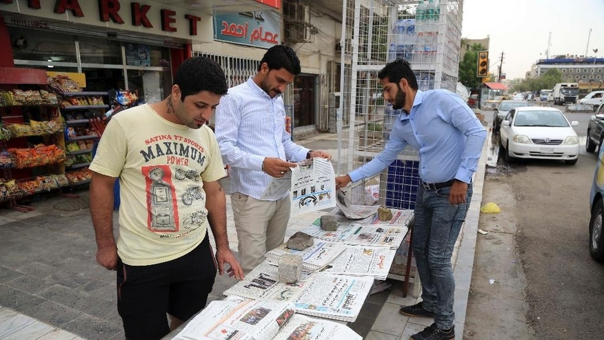 In this Thursday, May 5, 2016 photo, people read newspapers in Baghdad, Iraq. For nearly two years, U.S. airstrikes, military advisers and weapons shipments have helped Iraqi forces roll back the Islamic State group but many Iraqis still aren't convinced the Americans are on their side. (AP Photo/Karim Kadim)