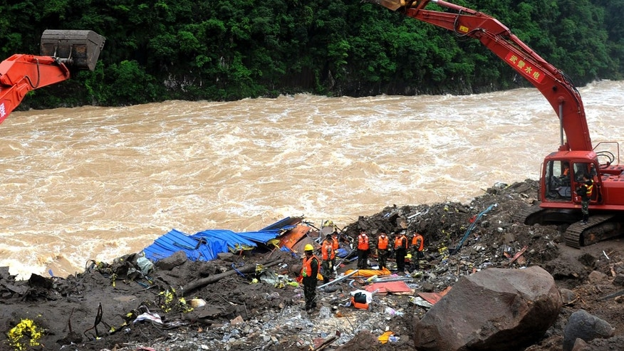 Rescuers pay respects to the body of a landslide victim in southeast China's Fujian province Monday.