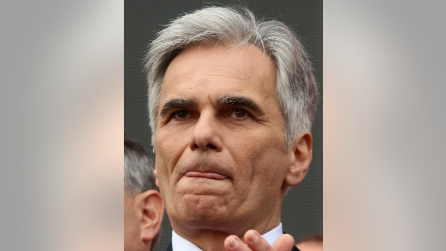 FILE - In this May 1, 2016 file photo Austria's Chancellor and head of the Social Democrats, SPOE, Werner Faymann listens to a speech during the traditional May Day celebrations oin Vienna, Austria, Sunday, May 1, 2016. Faymann announced Monday, May 9, 2016 that he will step back from all his posts. (AP Photo/Ronald Zak, file)