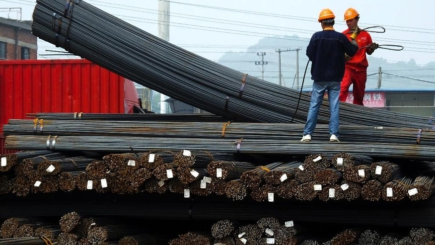 In this April 29, 2016 photo, workers load steel bars at a steel market in Yichang in central China's Hubei province. China's Cabinet has approved measures to boost exports in a move that might worsen tensions with trading partners that say Beijing is flooding their markets with unfairly low-priced steel and other goods. The announcement late Monday, May 9 comes as Beijing struggles to reduce a glut of goods in an array of industries and reverse an export decline that threatens to cause politically dangerous job losses. (Chinatopix via AP) CHINA OUT
