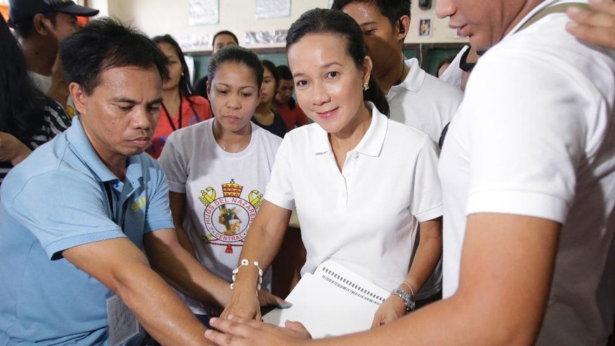 Philippine presidential candidate Grace Poe, center, votes at a polling center in San Juan, east of Manila, Philippines on Monday, May 9, 2016. Millions of Filipinos trooped to elections centers Monday to pick a new president, vice president and thousands of other officials amid tight security across the country. (AP Photo/Aaron Favila)