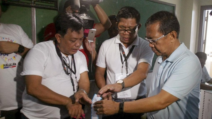 Presidential candidate and Philippine Vice President Jejomar Binay, right, checks on the vote receipt that comes out from the vote counting machine inside a polling center at the San Antonio National High School in Makati, Philippines Monday May 9, 2016. Millions of Filipinos began voting Monday in a presidential race where a foul-mouthed, crime-busting mayor is favored to win, but who the outgoing president says is a threat to democracy.(AP PHoto/Lino Escandor II)