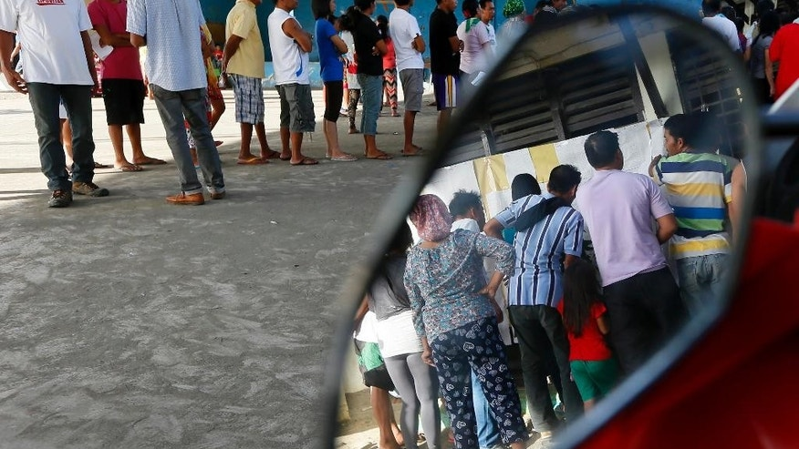 Filipinos queue up to vote for the country's presidential elections at the front-running presidential candidate Mayor Rodrigo Duterte's hometown of Davao city in southern Philippines Monday, May 9, 2016. Millions of voters are expected to troop to polling precincts all over the country to elect the successor of President Benigno Aquino III. (AP Photo/Bullit Marquez)