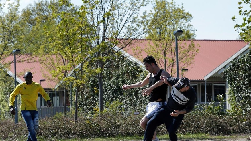 In this May 2, 2016 photo, men play soccer in front of residential houses at the Sumte refugee shelter in Sumte, Amt Neuhaus, northern Germany. The village of only 102 people housed up to 1,000 migrants. Six months after the first arrivals, not only have fears of violence and overtaxed utilities not materialized, but the shelter has brought benefits including dozens of jobs to the sleepy village of 102 people and the isolated rural region of northern Germany where it is located. (AP Photo/Michael Sohn)