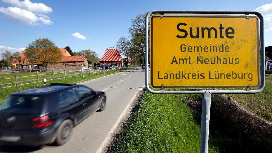 In this May 2, 2016 photo, a car drives past a town sign close to the Sumte refugee shelter in Sumte, Amt Neuhaus, northern Germany. The village of only 102 people housed up to 1,000 migrants. Six months after the first arrivals, not only have fears of violence and overtaxed utilities not materialized, but the shelter has brought benefits including dozens of jobs to the sleepy village of 102 people and the isolated rural region of northern Germany where it is located. (AP Photo/Michael Sohn)