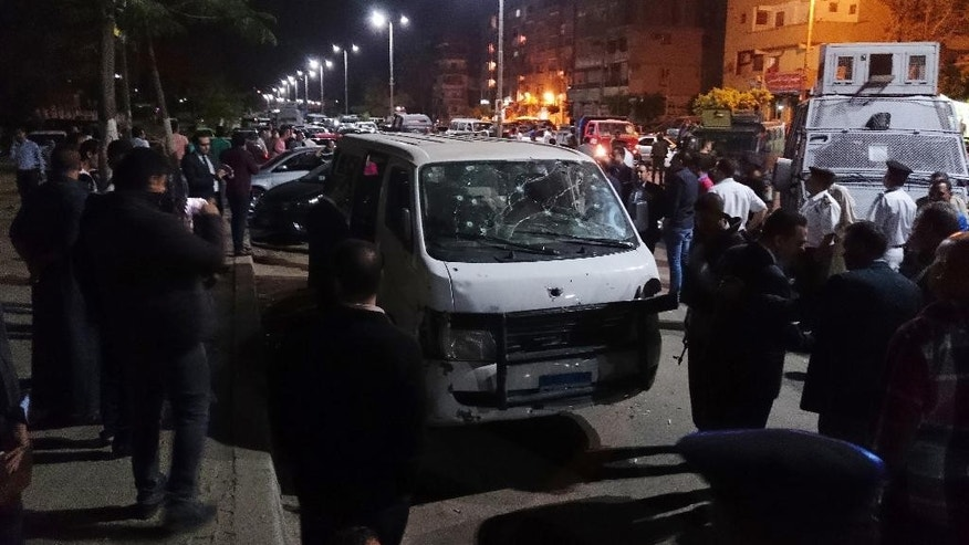 Egyptian police and civilians gather around the bullet-ridden microbus in the south Cairo neighborhood of Helwan on Sunday.