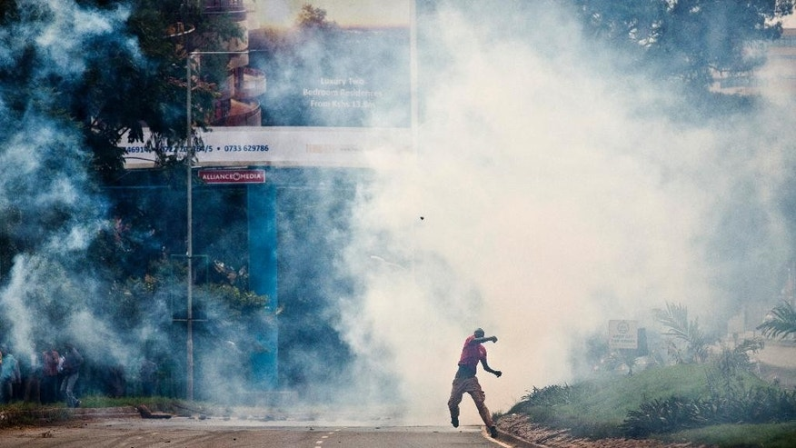 An opposition supporter standing amidst clouds of tear gas throws a rock towards riot police, during a protest in downtown Nairobi, Kenya Monday, May 9, 2016. Kenyan police have tear-gassed opposition supporters after some pelted police with rocks during a protest demanding the disbandment of the electoral authority over alleged bias and corruption. (AP Photo/Ben Curtis)