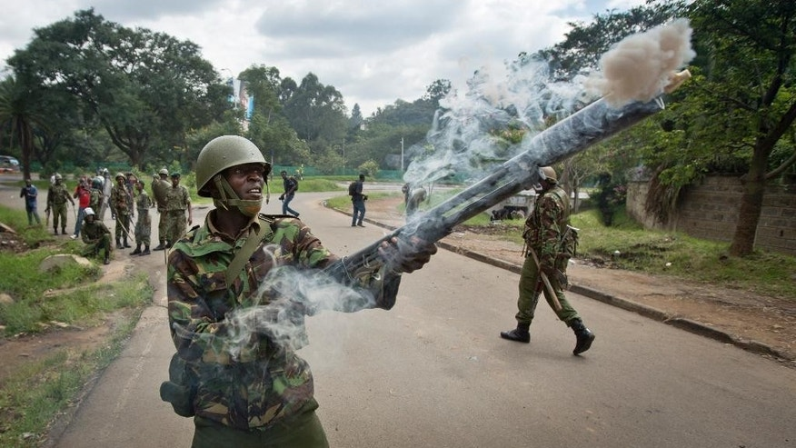 A riot policeman fires tear gas towards opposition supporters during a protest in downtown Nairobi, Kenya Monday, May 9, 2016. Kenyan police have tear-gassed opposition supporters after some pelted police with rocks during a protest demanding the disbandment of the electoral authority over alleged bias and corruption. (AP Photo/Ben Curtis)