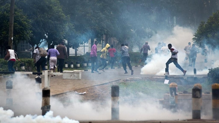 Opposition supporters run away from tear gas fired by riot police during a protest in downtown Nairobi, Kenya Monday, May 9, 2016. Kenyan police have tear-gassed opposition supporters after some pelted police with rocks during a protest demanding the disbandment of the electoral authority over alleged bias and corruption. (AP Photo/Ben Curtis)
