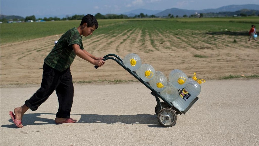 A boy pushes a  barrow with water at the northern Greek border point of Idomeni, Greece, on Monday, May 9, 2016. About 54,000 refugees and migrants are currently stranded in Greece as 10,000 are camped in Idomeni, after the European Union and Turkey reached a deal designed to stem the flow of refugees into Europe's prosperous heartland. (AP Photo/Petros Giannakouris)