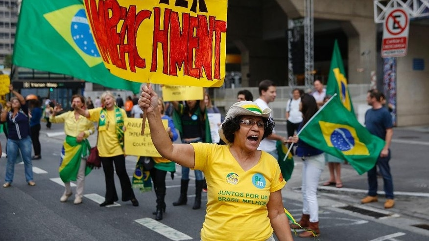 "A demonstrator holds a banner that reads in Portuguese ""There will be Impeachment"" during a protest demanding the impeachment of Brazil's President Dilma Rousseff  in Sao Paulo, Brazil, Monday, May 9, 2016. Brazil's Senate leader Renan Calheiros said on Monday the Senate will vote as scheduled on a motion to open an impeachment trial against President Dilma Rousseff, despite a sudden lower house about-face. (AP Photo/Andre Penner)"