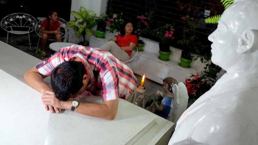 In this photo provided by Davao City Mayor's Office, leading presidential candidate Mayor Rodrigo Duterte visits the tomb of his late father Gov. Vicente Duterte at San Pedro Memorial Park in Davao city, southern Philippines early Tuesday, May 10, 2016. Soon after it became clear from the election count that Davao City Mayor Duterte will be the next president of the Philippines, he left his home at 3 a.m. Tuesday and went to the cemetery. At the tomb of his parents, he kneeled. And he wept. (Kiwi Bulaclac/Davao City Mayor's Office via AP)