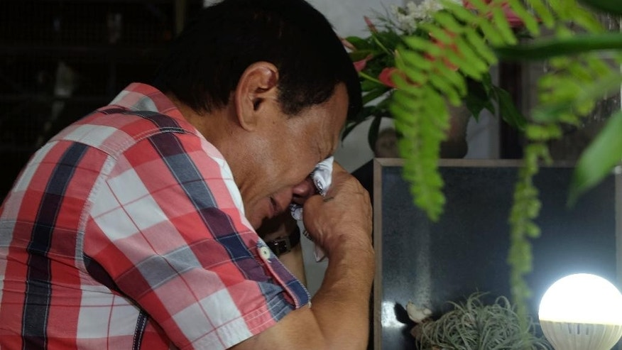 In this photo provided by Davao City Mayor's Office, leading presidential candidate Mayor Rodrigo Duterte wipes his tears as he visits the tomb of his late father Gov. Vicente Duterte at San Pedro Memorial Park in Davao city, southern Philippines early Tuesday, May 10, 2016. Soon after it became clear from the election count that Davao City Mayor Duterte will be the next president of the Philippines, he left his home at 3 a.m. Tuesday and went to the cemetery. At the tomb of his parents, he kneeled. And he wept. (Kiwi Bulaclac, Davao City Mayor's Office via AP)