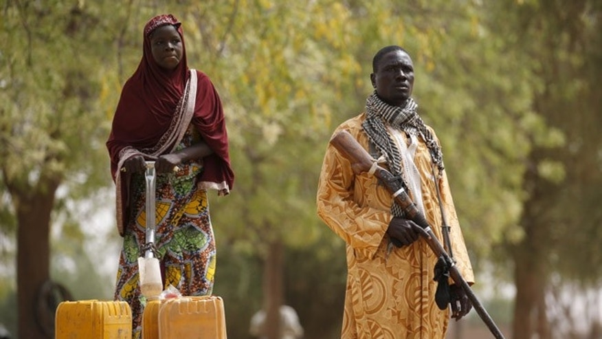 March: A member of a civilian vigilante group holds a hunting rifle while a woman pumps water into jerrycans in Kerawa, Cameroon. Kerawa is on the border with Nigeria and is subject to frequent Boko Haram attacks.