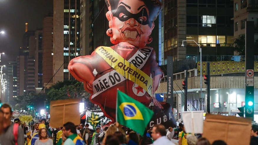 "People protest next to large inflatable doll of Brazil's President Dilma Rousseff wearing a presidential sash with the words ""Goodbye dear"" and ""Mother of Big Oil"" written in Portuguese, in Sao Paulo, Brazil, Monday, May 9, 2016. Brazil's Senate leader Renan Calheiros said on Monday the Senate will vote as scheduled on a motion to open an impeachment trial against President Dilma Rousseff, despite a sudden lower house about-face. (AP Photo/Andre Penner)"