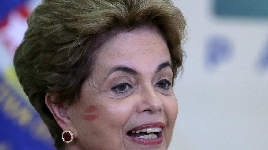 Brazil's President Dilma Rousseff's cheek is covered with a kiss, given to her as she entered an event where she announced the opening of new federal universities at Planalto presidential palace in Brasilia, Brazil, Monday, May 9, 2016. The acting speaker of the lower house of Brazil's Congress on Monday annulled last month's vote on impeachment, delaying and complicating the process that was widely expected to see Rousseff suspended later this week.  (AP Photo/Eraldo Peres)