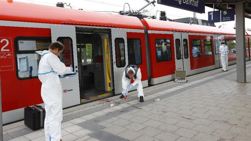 Police investigate the scene of a stabbing at a station in Grafing near Munich, Germany, Tuesday, May 10, 2016. Police said one person has died in a hospital after the stabbing. Police said the suspected assailant is a 27-year-old German national.  (AP Photo/Matthias Schrader)