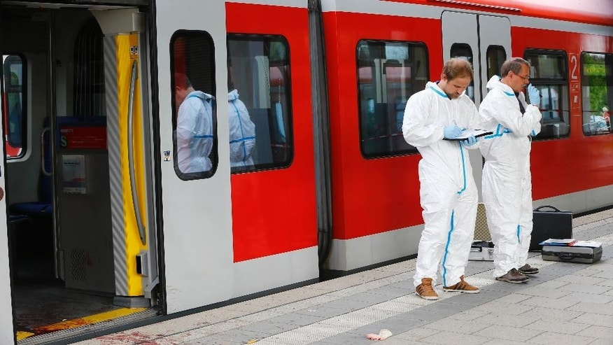 Police investigators take notes at the site of a stabbing at a station in Grafing near Munich, Germany, Tuesday, May 10, 2016. Police said one person has died in a hospital after the stabbing. Police said the suspected assailant is a 27-year-old German national.  (AP Photo/Matthias Schrader)