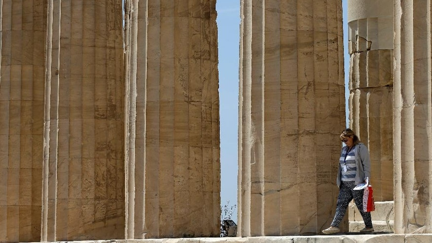 A woman exits the 2,500-year-old Parthenon temple on the Athenian Acropolis, on Monday, May 9, 2016. European finance ministers are trying to break a deadlock over whether to provide Greece with the next batch of bailout loans, which it needs to avoid bankruptcy this year, and forgive some of its debts. (AP Photo/Thanassis Stavrakis)